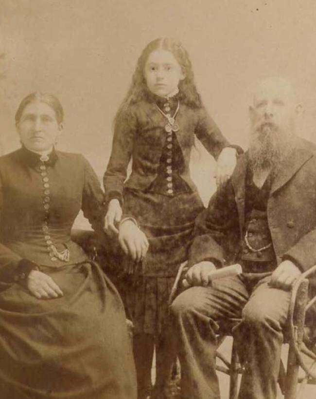 In this photograph, the girl standing in the middle is the deceased. The photographer attempted to make her look more alive by drawing on her pupils.